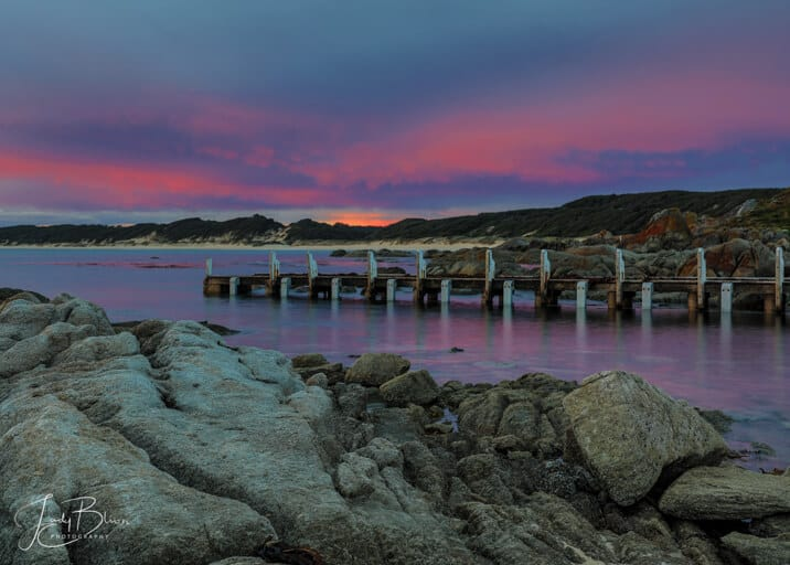 Cape Conron Gippsland Australia at sunset. The jetty is coming out of the water with the reflection of the purple and blue sky. The rocks are a stark grey against all of the colours in the picture
