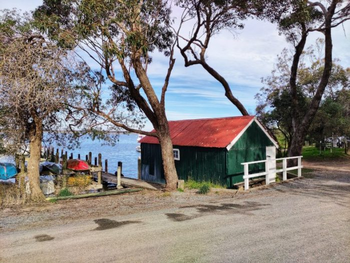 a green and red boathouse with a jetty stretching into the water at Nungurner