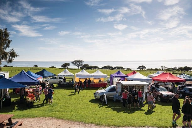 a green rural paddock with tents and people . A farmers market at Phillip Island