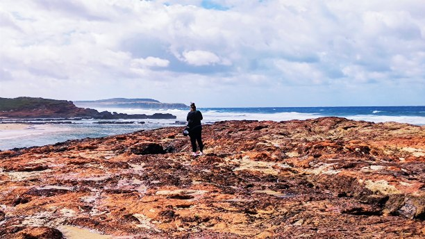 A lady looking at the beach while standing on some rocks at Forest Cave in Phillip Island