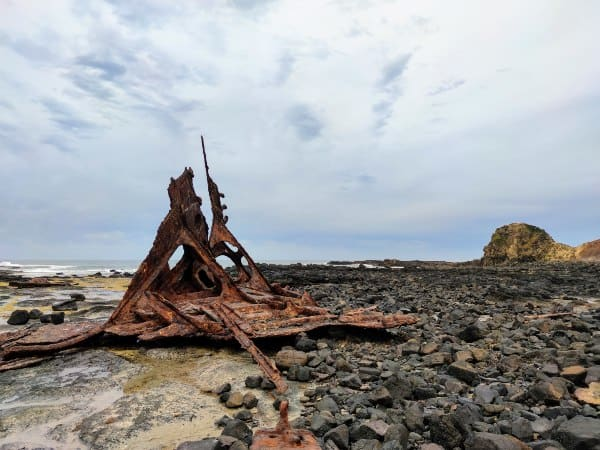 a rocky beach area with a decaying part of a shipwreck